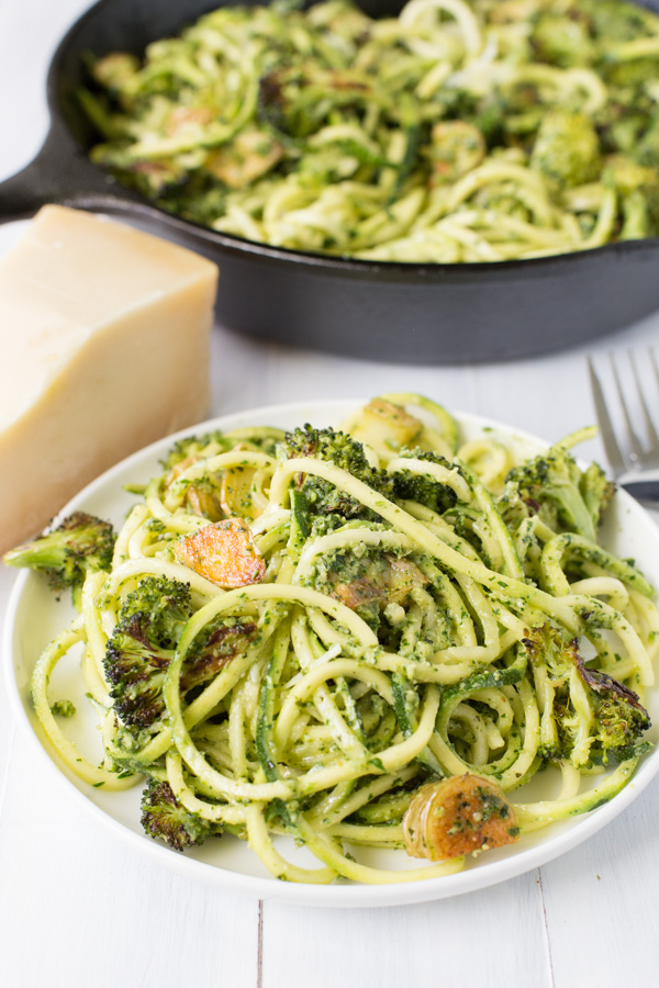 Pesto Zoodles with Roasted Broccoli and Crispy Potatoes is a meatless main FULL of flavor! Zoodles, roasted broccoli, and crispy yellow potatoes are tossed in a cilantro/parsley/pine nut/pepita pesto sauce. A great Meatless Monday option! | www.heartandstove.com