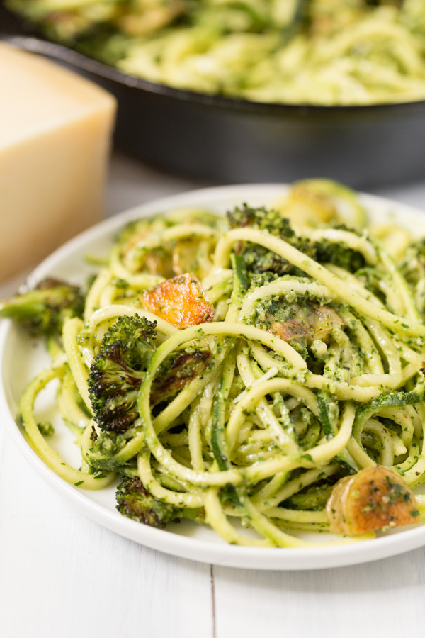 Pesto Zoodles with Roasted Broccoli and Crispy Potatoes is a meatless main FULL of flavor! Zoodles, roasted broccoli, and crispy yellow potatoes are tossed in a cilantro/parsley/pine nut/pepita pesto sauce. A great Meatless Monday option!   www.heartandstove.com