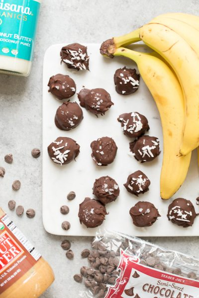Frozen Chocolate Dipped Banana Bites - a cool and healthy summer treat! Banana slices are topped with peanut butter or coconut butter, covered in chocolate, and sprinkled with flaky sea salt and/or shredded coconut.   www.heartandstove.com
