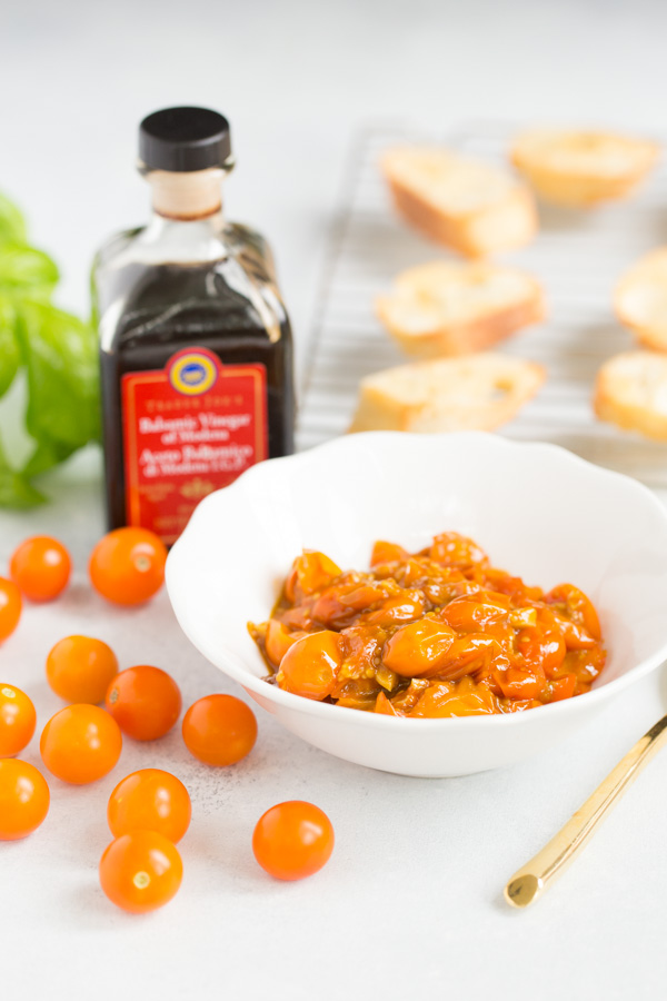 """Caramelized Cherry Tomato Crostini - the perfect appetizer to make the most of late summer produce.Sungold cherry tomatoes are """"caramelized"""" with olive oil and balsamic vinegar till sweet and jammy, then spooned onto crisp baguette slices and topped with fresh basil. 