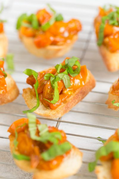 """Caramelized Cherry Tomato Crostini - the perfect appetizer to make the most of late summer produce.Sungold cherry tomatoes are """"caramelized"""" with olive oil and balsamic vinegar till sweet and jammy, then spooned onto crisp baguette slices and topped with fresh basil.   www.heartandstove.com"""