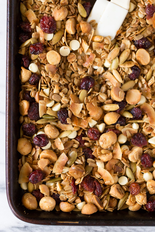 Coconut Cranberry White Chocolate Macadamia Nut Granola - the title says it all! Homemade granola loaded with oats, nuts, seeds, dried fruit, and a bit of white chocolate!   www.heartandstove.com