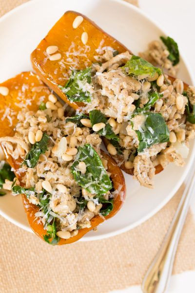 Turkey and Farro Stuffed Honeynut Squash is full of fall flavor! A mixture of ground turkey,farro, kale, parmesan cheese, and seasoning top roastedhoney nut squash for a healthy, protein and fiber packed meal. It's like healthy Thanksgiving in one bite!   www.heartandstove.com